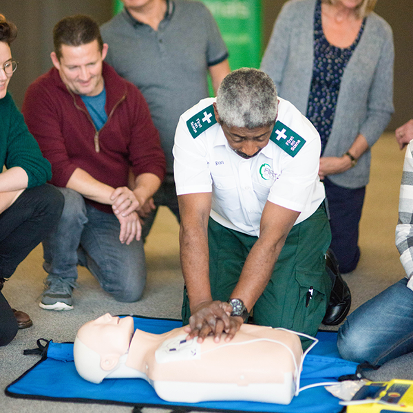 First On Scene First Aid Instructor Demonstrating CPR On A Dummy